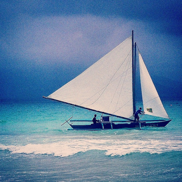 Boat heading out from the beach on Boracay Island, Philippines as the typhoon rolls away in the distance